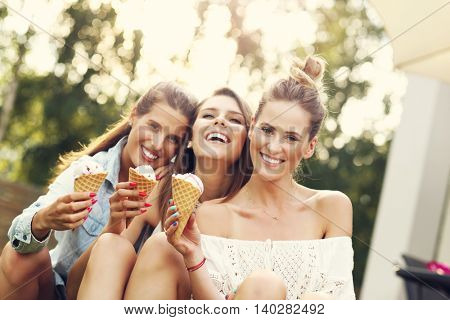Picture presenting happy group of friends eating ice-cream outdoors