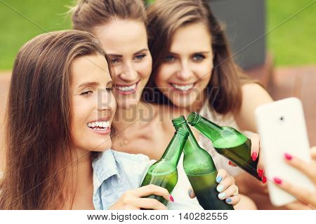 Picture presenting happy group of friends having a beer outdoors and taking selfie