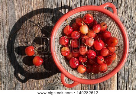 Cherries in a strainer on wooden background in the sunlight top view