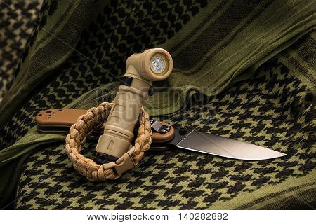 Composition of angle-head flashlight paracord bracelet and folding knife lying on shemagh close up shot