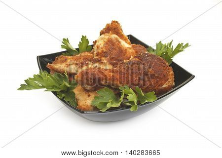Fried Chicken Pieces Coated With Breadcrumbs With With Parsley On A Black Plate. Isolated On White B