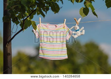 Baby clothes hanging on the clothesline in garden