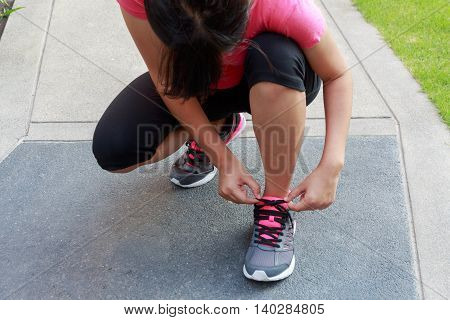 Woman tying laces running shoes getting ready for jogging - Running or jogging exercising concept
