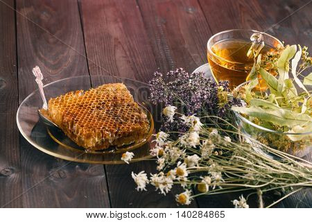 Golden Honeycomb With Honey And Tea Linden Flowers On Wooden Background