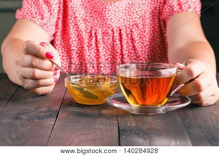 Woman Eat Honey And  Cup With Green Tea On Old Wooden Table