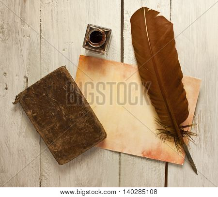 Photo of sheet of aged paper with quill pen bottle of ink and old notebook shot from above on wooden background texture slightly toned; concept of studying or writing; vintage objects