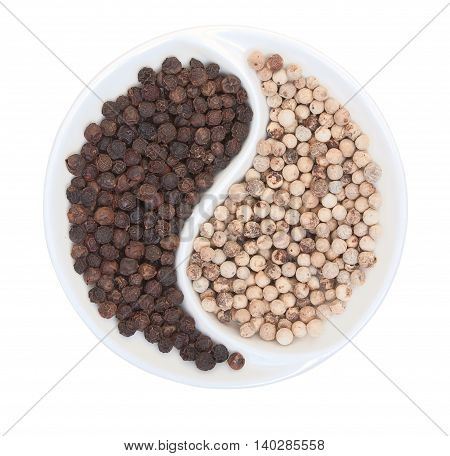 Grains Of Dry White And Black Pepper On A Plate Isolated On White Top View