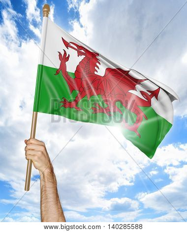 Person's hand holding the Welsh national flag and waving it in the sky, 3D rendering
