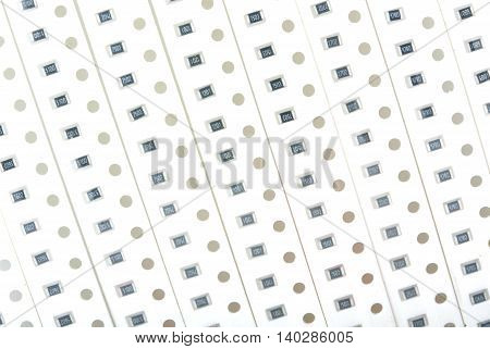 Perforated tapes with SMD chip resistors for soldering by robot on PCB board close up top view