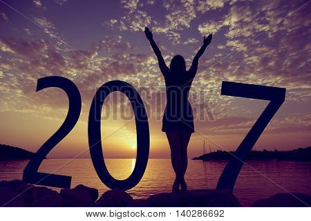 Happy new 2017 year card. A girl standing on a beach watching the sunset standing as a part of 2017 sign