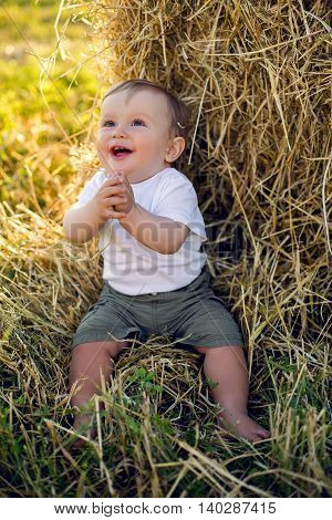 gay boy kid blonde in white tank top sitting on a field of hay next to the stack during sunset