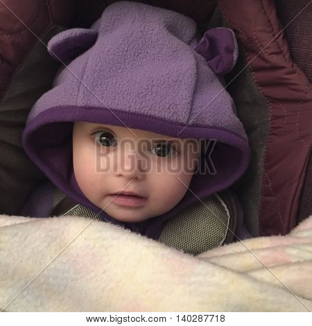 Toddler in a winter clothing and blanket looking at camera