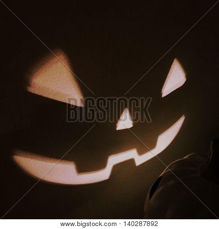Halloween Jack o Lantern shining on a wall - Instagram filter effect