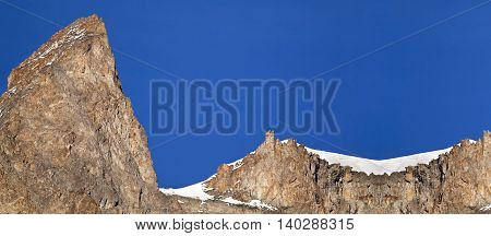 Website banner of snowy mountain rocks in the blue sky with copy space