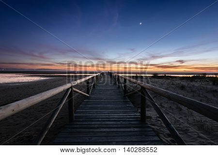 A boardwalk at night by the sea. You can still see the awesome orange and golden colors of the sunset but the moon is already high in the sky.