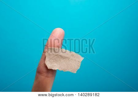 Hand holding yellow note reminder on finger with copy space for ad on blue background