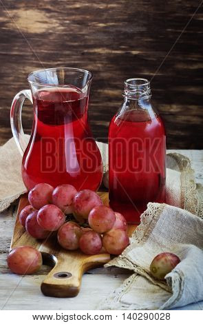 Fresh grape juice in a glass pitcher and ripe berries on the table. Rustic style. Health and diet food. Selective focus