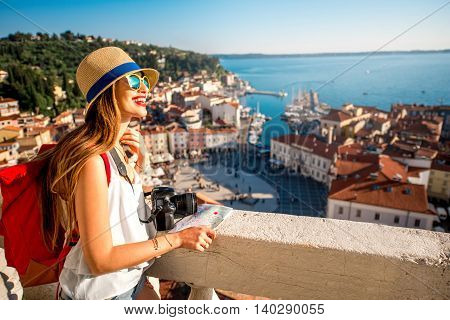 Young female traveler with red backpack and hat enjoying the view from George's tower on Piran old town. Traveling in Slovenia