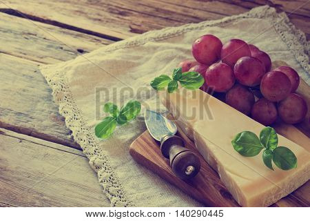 Fresh parmesan cheese and ripe grapes on a table. Tinted image. Health and diet food. Selective focus