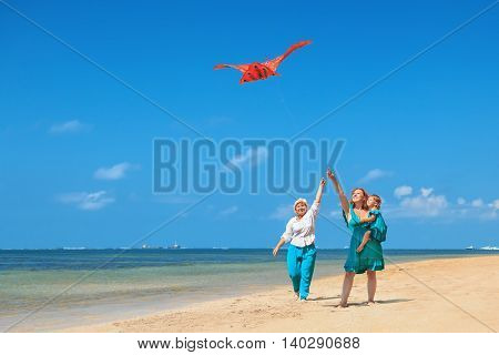 Happy family has fun on beach - grandmother mother and baby girl walk along ocean surf. Senior woman runs with flying red kite. Active parents and people activity on summer vacation with children.