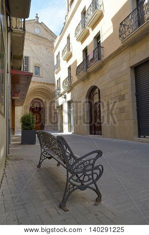 Iron bench in front of the Romanesque portal of the church of Gandesa (Catalonia, Spain)