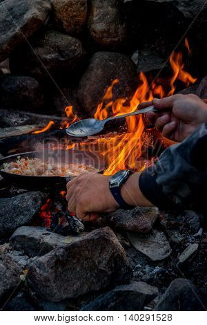 The Man Cooking Food On A Fire.