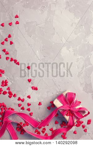 Festive background. Gift box and many little decorative red hearts on textured grey concrete. Flat lay with copy space. Toned image.