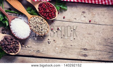Red white and allspice pepper and sea salt in wooden spoon on aged wooden background. Food ingredient. Selective focus. Place for text. Flat lay. Top view. Toned image.