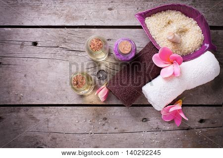 Wellness or spa setting. Bottles with aroma oil sea salt towels and pink plumeria on vintage wooden background. Selective focus. Place for text.