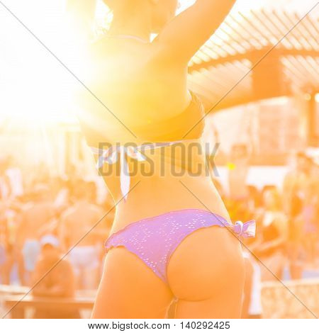Sexy hot girl wearing brazilian bikini dancing on a beach party event in sunset. Crowd dancing and partying at poolside in background. Summer electronic music festival. Hot summer party vibe.