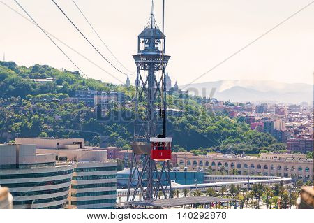 Red cabin cable car against the background of the city of Barcelona. View overlooking the town.