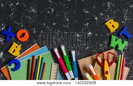 School accessories stationery on dark background. Top view free space for text. Concept of education and training