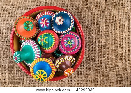 Still life shot showing top view of pottery lids stacked in a pottery bowl on sackcloth background