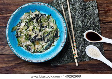 Asian food. Asian salad with seaweed nori, cucumber, white sesame seeds and soya in blue bowl on wooden rustic background. Top view