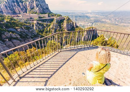 Female traveler enjoy the view of Montserrat monastery near Barcelona. Panorama from the top of the mountain. Spain.