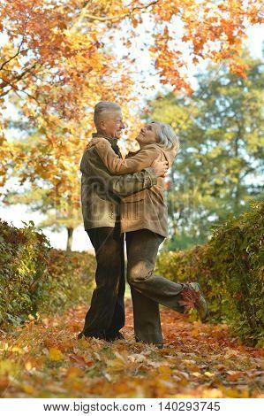 Elderly couple smiling together over natural background