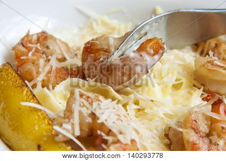Fettuccine Pasta with Shrimp cheese and lemon slice. Focus on fork with shrimp.