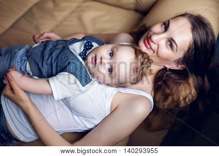young happy mother in white tank top laying with my son on a light sofa in the apartment
