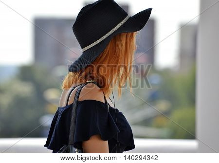 summer red-haired girl in a black hat and a black tank top hand holds her hat