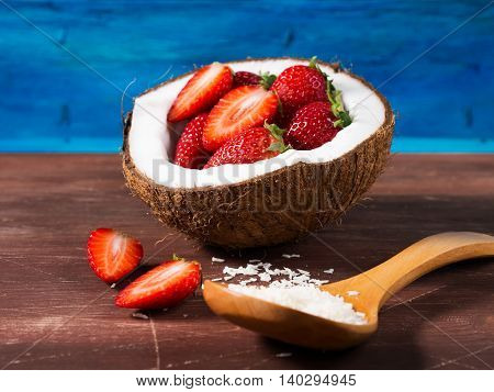 Coconut Shell With Strawberries On Rustic Background