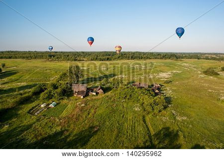 colorful balloons flying over the village fields and forest