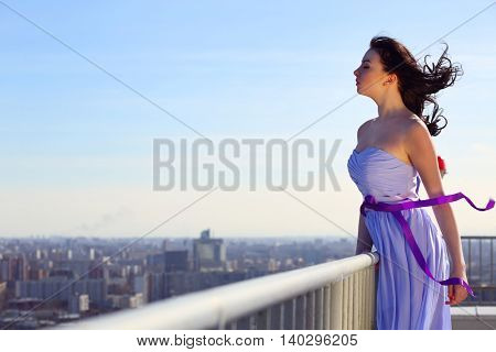 Girl brunette in blue dress with closing eyes stands on roof of tall building on wind