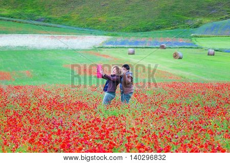Castelluccio di Norcia Italy - July 16 2016: Two girlfriends taking a selfie in a blooming poppy field. In the background the valley and some bales of hay harvest.