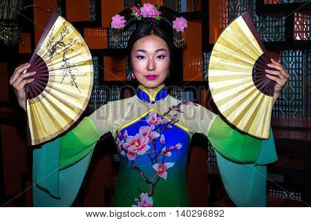 Chinese woman blue and green dress traditional cheongsam close up portrait with fans