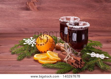 Mulled wine, fir branches, fresh orange, spices and snowflake on wooden table