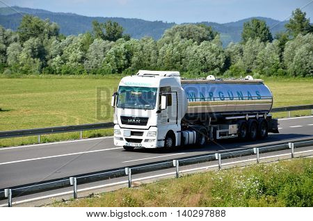 Dolny Hricov, Slovakia - June 29, 2016: White MAN truck coupled with tank semi-trailer drived on slovak D1 highway in countryside.
