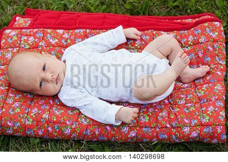 Newborn baby laying on a red blanket on green grass seriously looking into the camera
