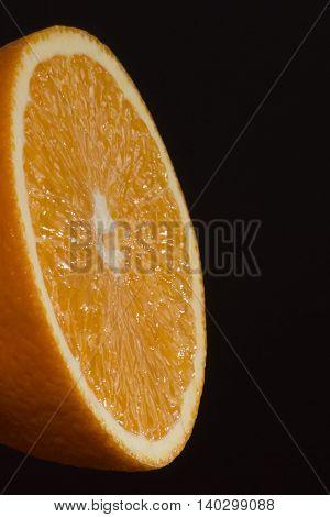 Half of orange on dark background. Studio photo