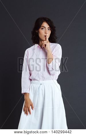 Attractive young woman standing over grey background and make silence gesture