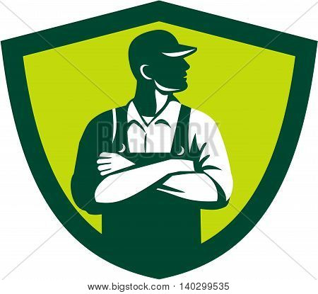 Illustration of an organic farmer wearing hat and overalls arms folded looking to the side viewed from front set inside shield crest on isolated background done in retro style.